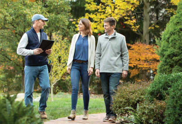 A landscape designer talks with a couple of homeowners about their landscaping project