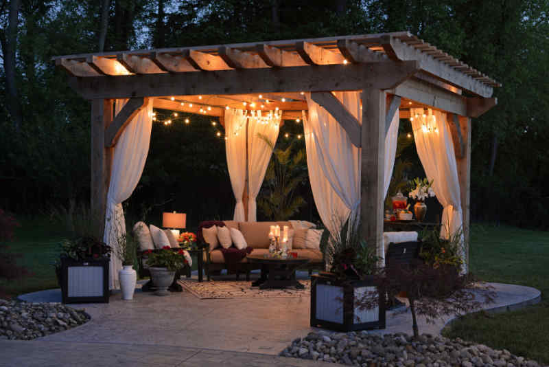 Faux wood patio and pergola with lighting and sheer curtains
