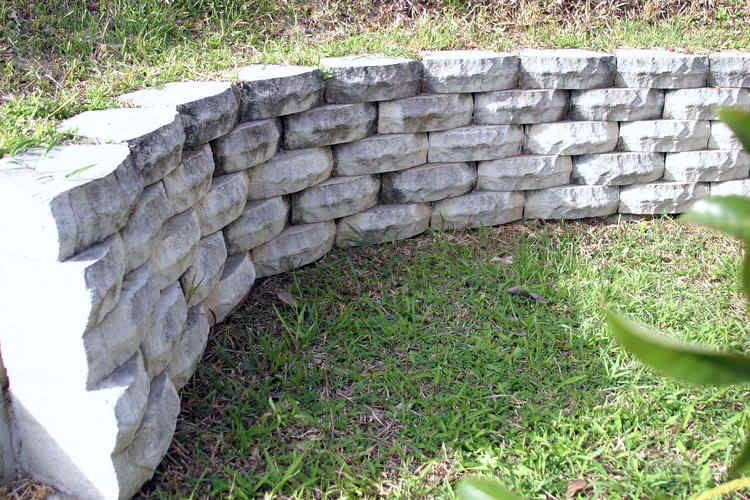 Natural block curved retaining wall and green grass