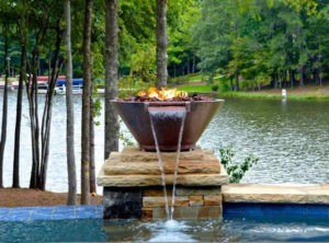 Fire pit on a natural stone pedestal surrounded by a water fountain