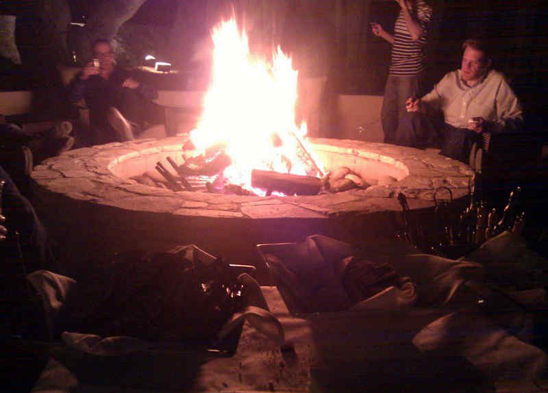 Friends seated around a blazing outdoor stone fire pit