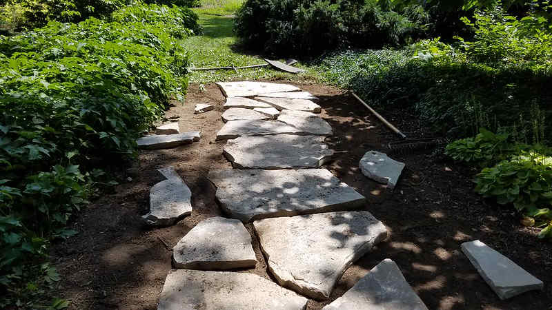 Natural flagstone being laid for a garden walkway path.