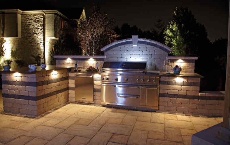 Custom outdoor kitchen lighting on a patio at night.