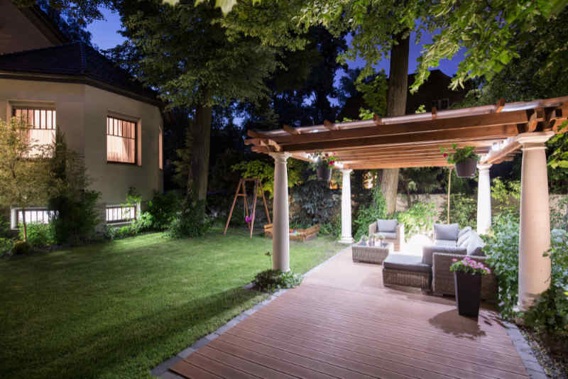 Backyard living space with a covered pergola accented with low voltage landscape lighting
