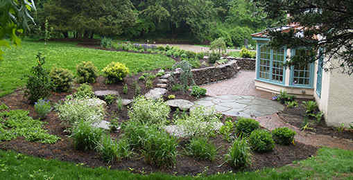 Attractive rain garden protecting patio from yard drainage.