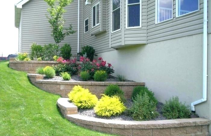 Lawn terraces with raised flower beds help slow rain drainage and erosion beside a house with a sloped yard.