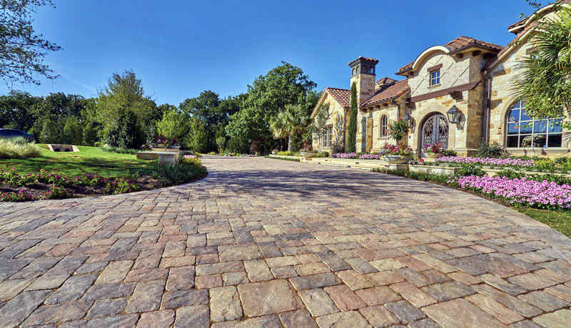 Home with nice driveway made of colorful pavers