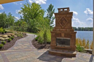 Patio and outdoor fireplace surrounded by landscaping by a lake