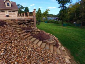 Steep hilly yard with retaining walls, stone steps, and patio at Lake of the Ozarks