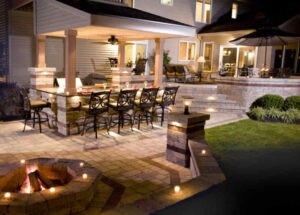Outdoor backyard patio, firepit, and landscaped space lit up at night at Sunrise Beach, MO