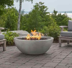 Concrete fire bowl on patio with natural greenery and a lake in the background
