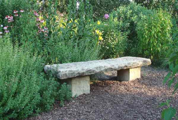 Natural stone bench surrounded by flowers and plants in summertime