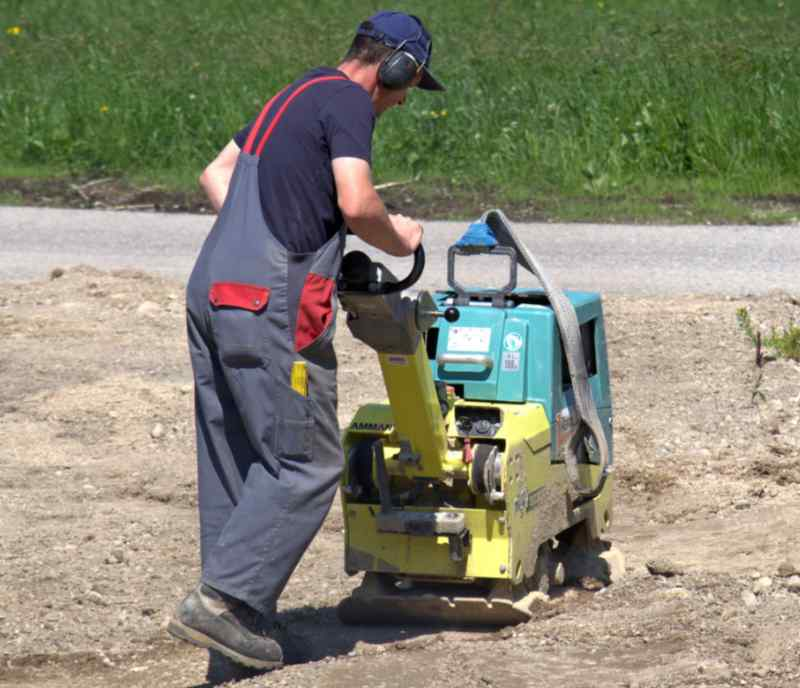 Man working with a vibrating wacker plate to flatten driveway area for paver installation.