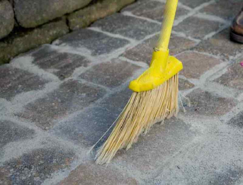 Broom sweeping polymeric sand into cracks between hardscape pavers
