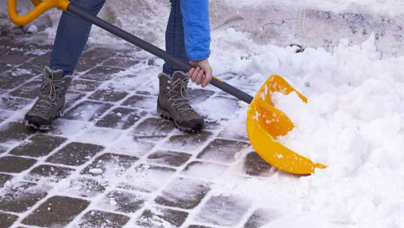 Man removing snow from pavers with a large plastic shovel