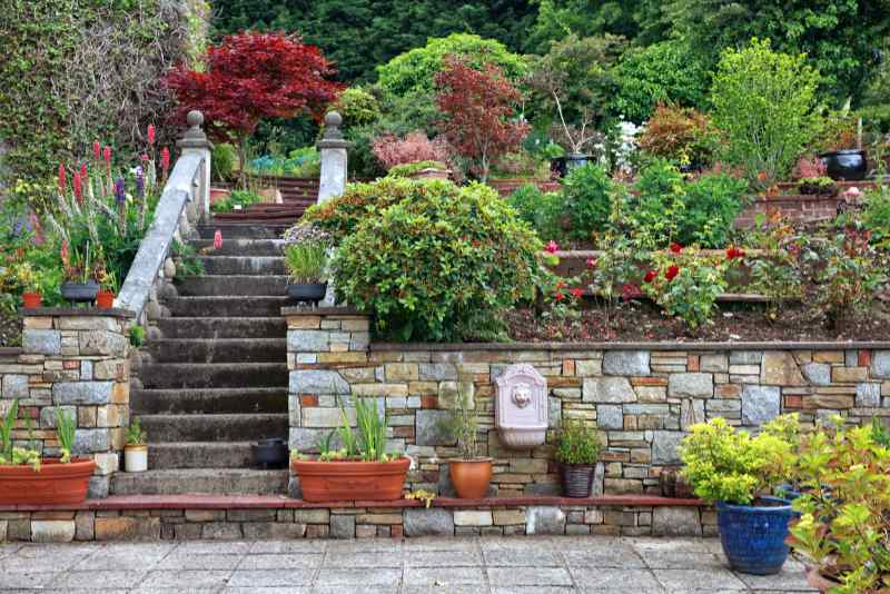 Natural stone steps and retaining wall for landscaping on a hill, with planter and garden border framing home entrance. Beautiful hardscape, colorful landscape design.