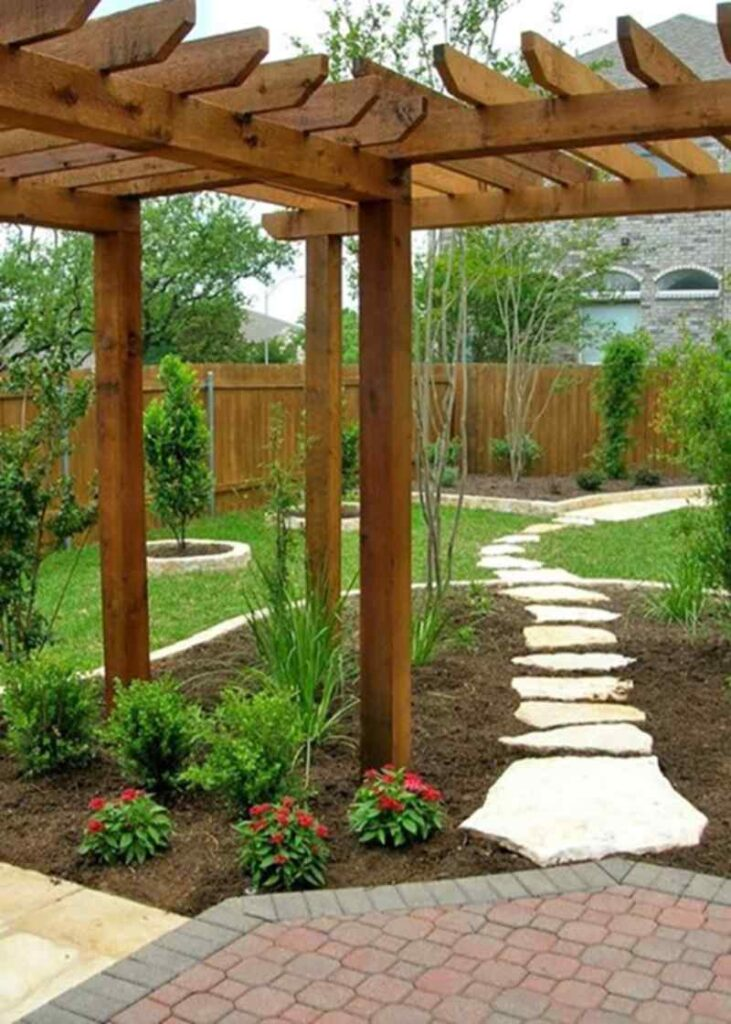 Nice landscape design idea with mulch, flagstone pavers and a patio with a pergola