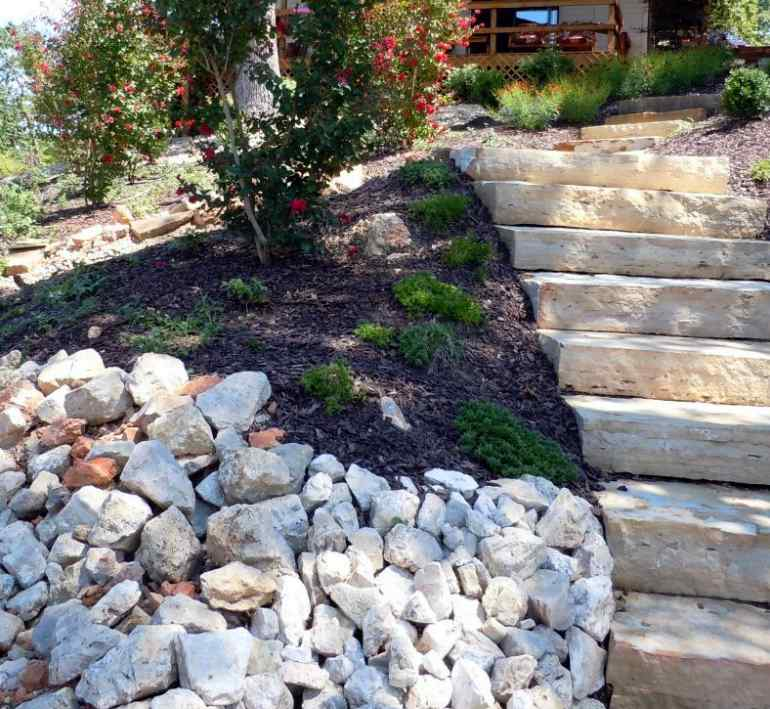 Natural stone steps down a slope and landscape rock creating erosion control