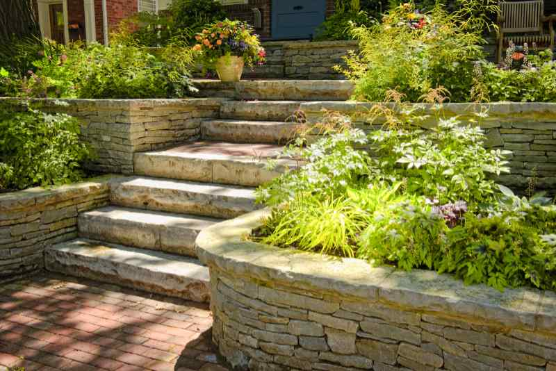 Natural stone landscaping and hardscape in home garden with stairs and retaining walls