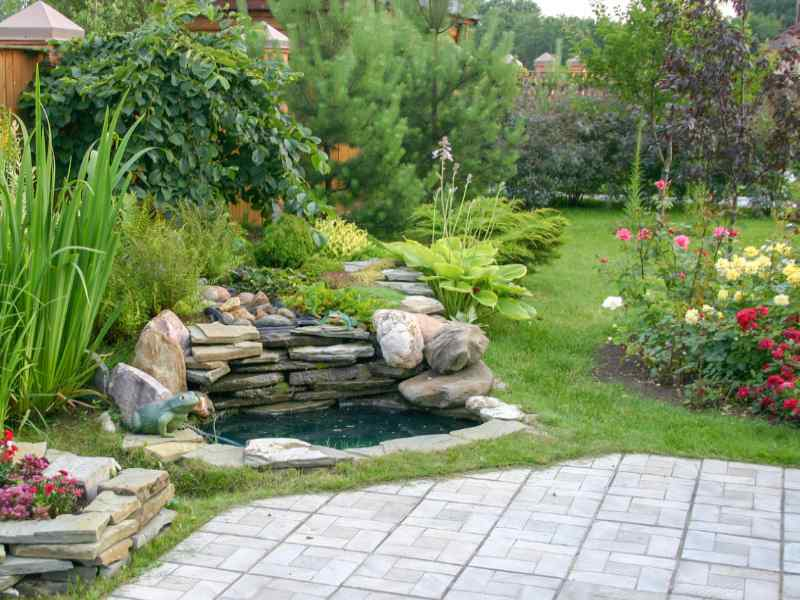Landscape design with waterfall, patio, and colorful plants