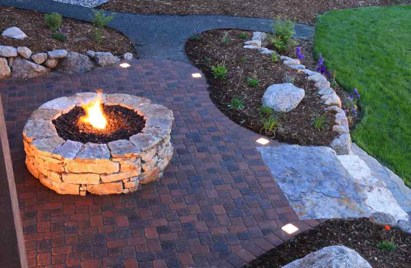 Overhead view of fire pit and backyard patio landscape pavers at dusk. Paver patio has built in lighted pavers.